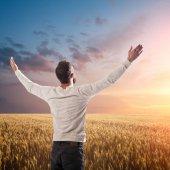 Praying over wheat field sunset