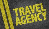 Strada asfaltata con agenzia di viaggi cartello giallo