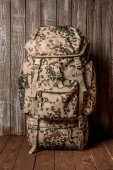 Travel backpack khaki color on a wooden background