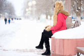 Lonely woman sitting on the bench in park in wintertime