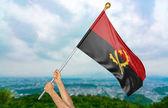 Mladý muž ruce hrdě mává Angola státní vlajka na obloze, část 3d vykreslování