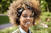 Outdoor headshot of black smiling female student going to University passing by city park, looking cheerful and self-confident, enjoying warm spring day, isolated on blurred background of green nature