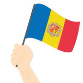Hand holding and raising the national flag of Andorra
