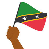 Hand holding and raising the national flag of Saint Kitts and Nevis