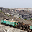 Постер, плакат: Train at the iron ore opencast mine is going for loading iron or
