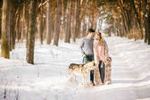 Outdoor happy couple in love posing with dog in cold winter weather. Young boy and girl having fun outdoor. Boho