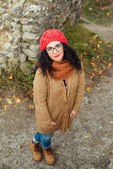 Portrait of young Caucasian woman in red knitted hat outdoors in park.