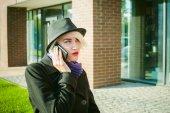 Portrét mladé krásné ženy s bílými vlasy, v černém kabátě, sukni a černém klobouku, mluví o mobilní telefon na ulici. telefonní komunikaci, spolupráci, příjemný rozhovor o podnikání