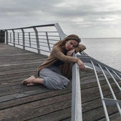 Sad girl sitting on the old berth
