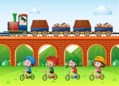 Scene with trains on bridge and kids riding bike in the park illustration
