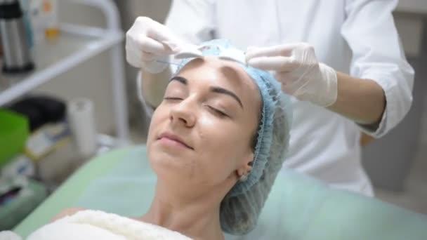 kosmetička klade ochranné brýle na pacienta