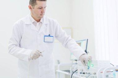 proctologist holding Ligador hemorroidal