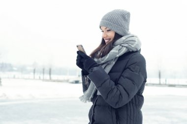Girl with a mobile phone in winter
