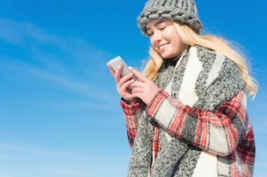 Woman with phone outdoors in winter