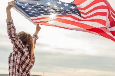 young beautiful woman holding USA flag