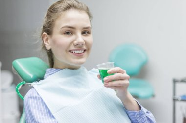 female patient rinsing mouth with dentist in background at clini