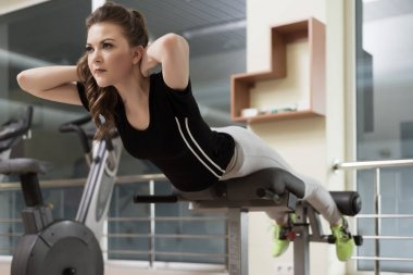 Sports young woman doing exercises on trainer back machine
