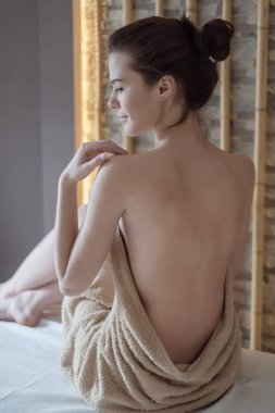 young woman sitting on a bed in a towel