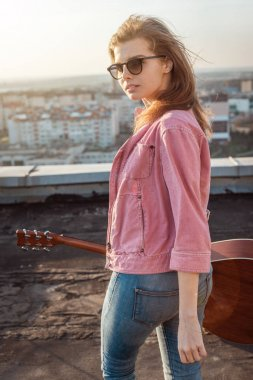 young beautiful woman with a guitar on the roof