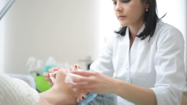 Kosmetička krém do obličeje a masáže žena s kosmetické ošetření v lázních. Profesionální kosmetička použití masky na ženě na salon krásy. Kůže obličeje postupy čištění kosmetologie