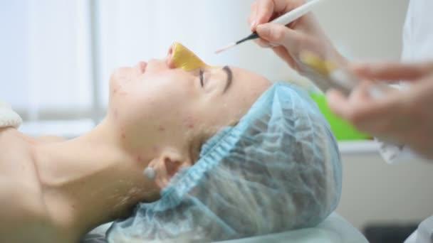 Kosmetikerin anwenden Gold Gesichtsmaske auf das Gesicht, Frau, die kosmetische Behandlung im Spa. Professionelle Kosmetikerin auf weiblich im Schönheitssalon. Haut-Verfahren reinigen Kosmetik.