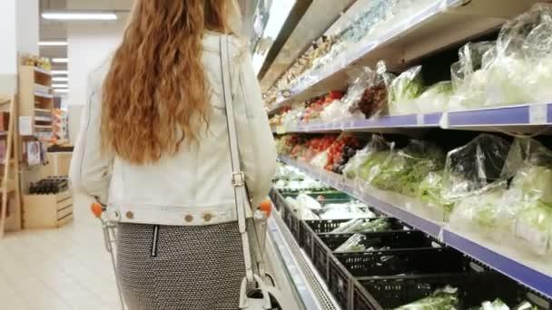 Žena nakupování. Mladá žena zvolí zelenina na pultech