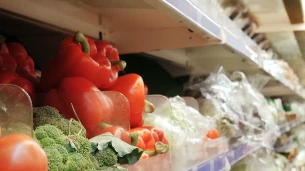 Mladá žena si vybírá nákup paprika červená paprika na pultech. trh s potravinami čerstvá zelenina