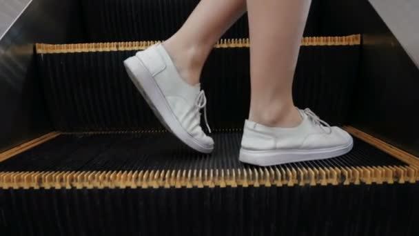 žena člověk na eskalátory v moderním interiéru městského, nohy krokování přes kameru do pohyblivého schodiště jako Snadná příležitost nebo úspěch konceptu