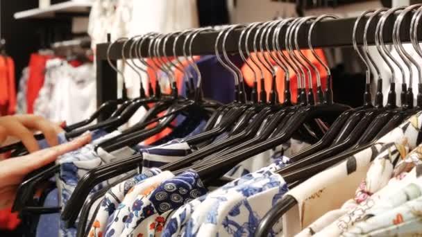 Žena v obchodě vypadá prostřednictvím košile, které jsou zavěšené na stojany. ruce se přeběhnout stojan na oblečení, procházení v butiku. Čelní pohled s nosič focus.