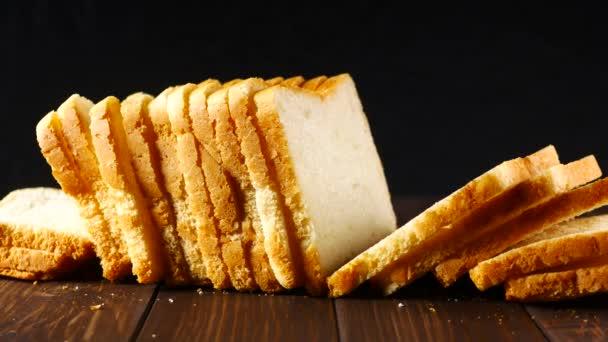 Sliced loaf of bread on black background