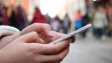 Close-Up Shot Of Womans Hands Using mobile phone In Busy Public Place