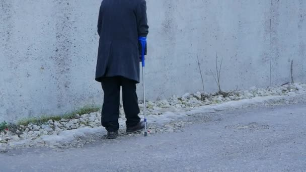 elderly handicapped people background. old man walks in public with crutches.