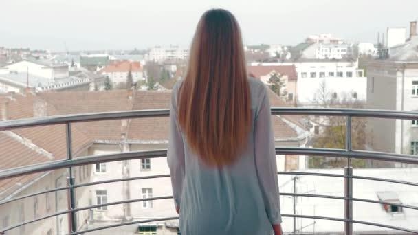 eine junge Frau geht auf den Balkon und bewundert die Landschaft der Stadt