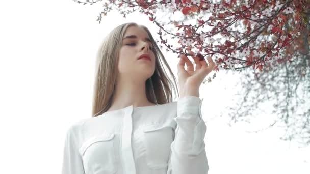 Letní životní styl módní portrét mladých krásná blondýna stylové hipster ženy nosit bílou košili na pozadí Kvetoucí strom