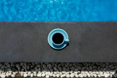 Blue cup of hot black coffee