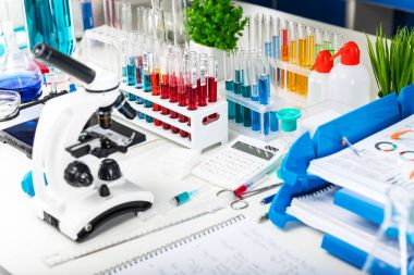 Creative abstract chemistry development, medicine, pharmacy, biology, biochemistry and research technology concept: table with scientific chemical laboratory equipment - microscope, test tubes with color liquid substance samples, vials, flasks, repor stock vector