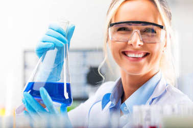 Happy young attractive female scientist with protective eyeglasses and gloves holding a flask with blue liquid substance in the chemical research laboratory stock vector