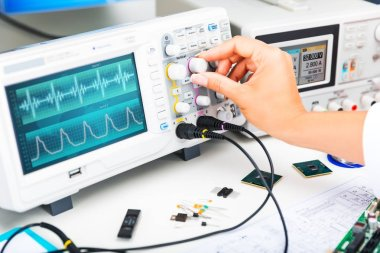 Digital oscilloscope is used by an experienced electronic engineer in the laboratory stock vector