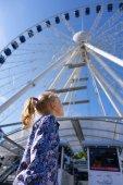 Hezká holčička se dívá na ruském kole proti modré obloze
