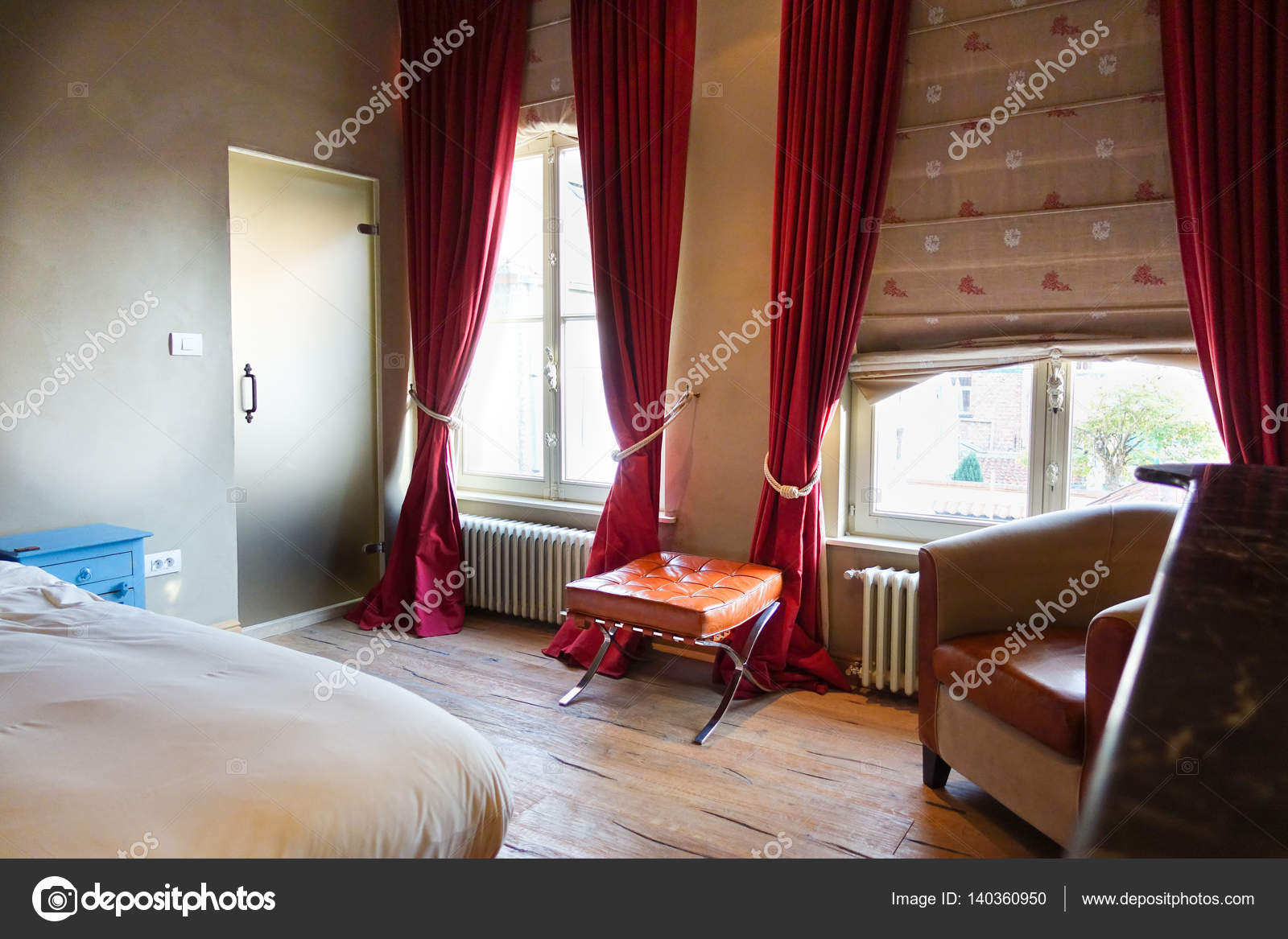 Comfortabele slaapkamer met grote ramen en houten vloeren ...
