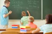 Fotografie Školní chlapec se svým učitelem na tabuli na hodině matematiky v