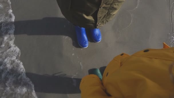 Two children standing in water of cold Baltic sea in colorful rubber high boots