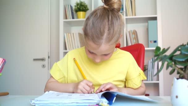 Lassított felvétel egy imádnivaló kis iskolás lányról, aki házi feladatot csinál otthon az asztalnál.