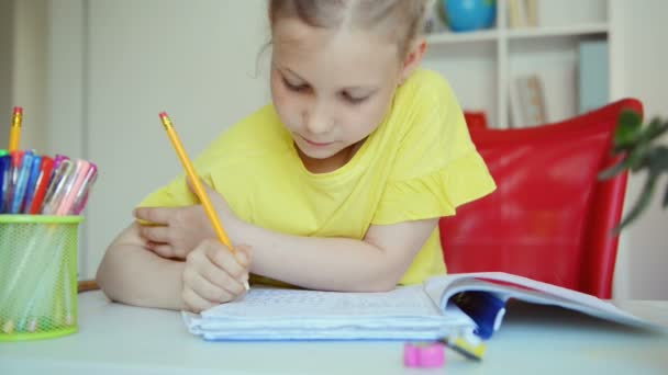 Video of adorable little schoolgirl doing homework at the desk at home