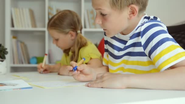 Két aranyos iskolás fiú és lány együtt csinálják a házi feladatot otthon.