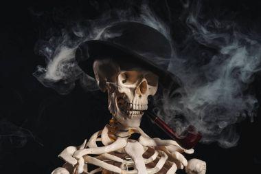 Skeleton in bowler hat smoking pipe