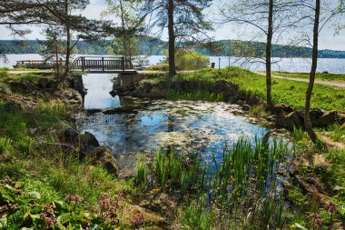 Picturesque landscape with bridge in park on shore of lake in Karelia