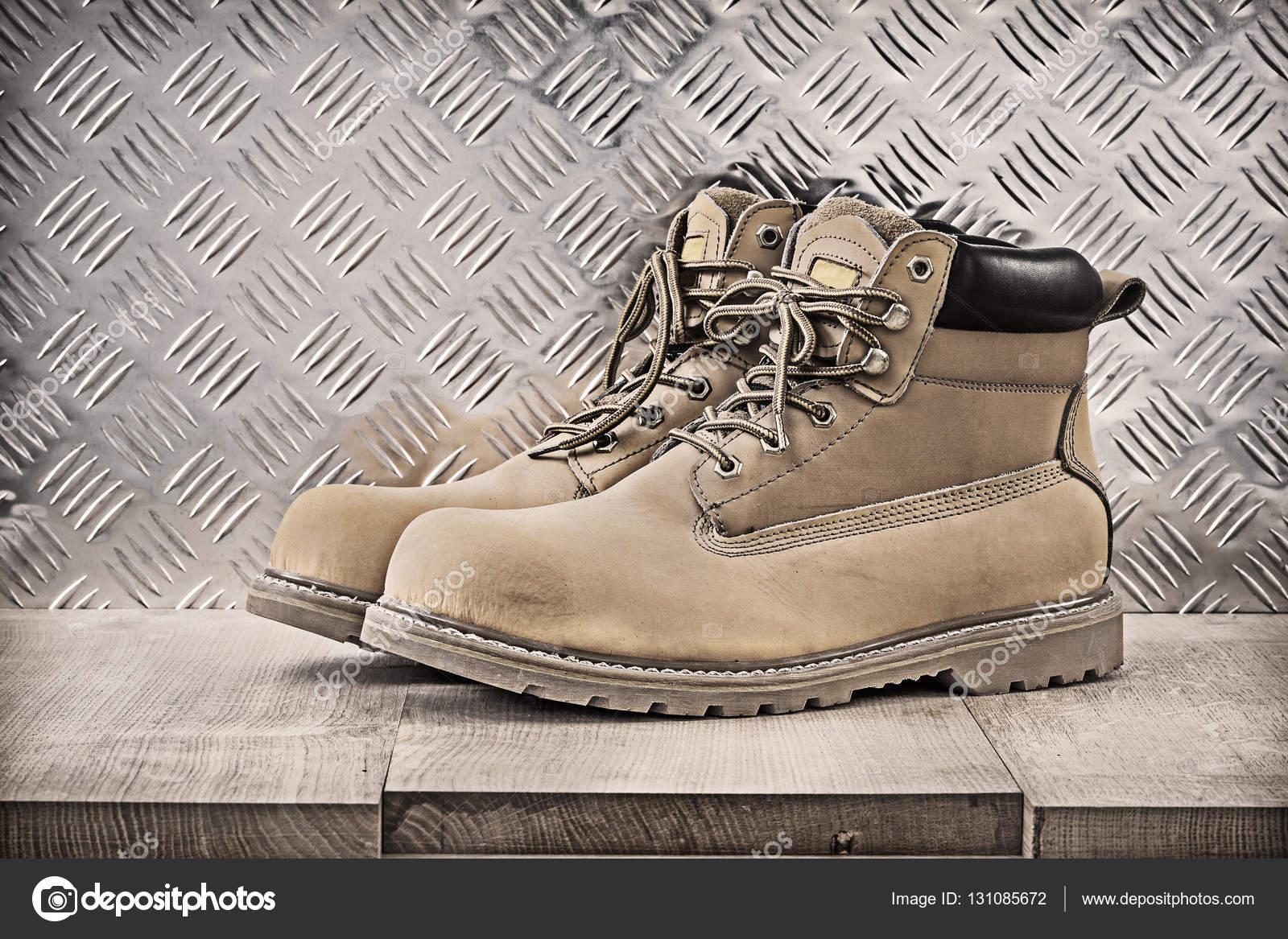 aa0e9b74649 Ζευγάρι μπότες ασφαλείας στην ξύλινη σανίδα και διοχετεύεται λαμαρίνας,  κατασκευαστική αντίληψη — Εικόνα από ...