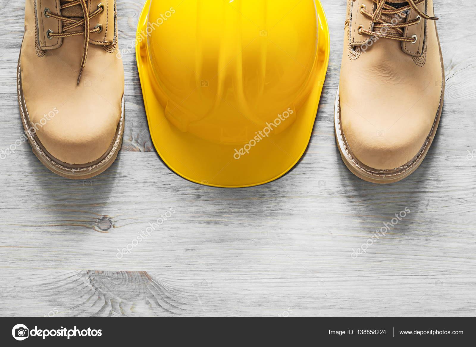 8e985420643 Ζευγάρι των αδιάβροχες μπότες κράνος με βάση ξύλινη σανίδα constru– εικόνα  αρχείου