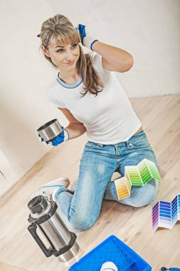 young female worker sitting on floor with coffee and color palet